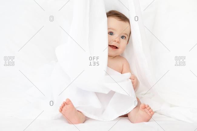 Cute happy baby playing peekaboo behind white sheet