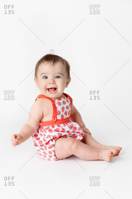 Side view of smiling baby wearing strawberry outfit on white background