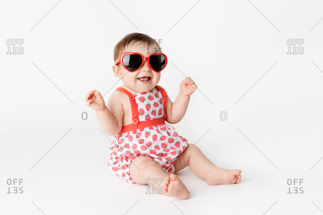 Cute smiling baby with heart-shaped glasses and strawberry outfit