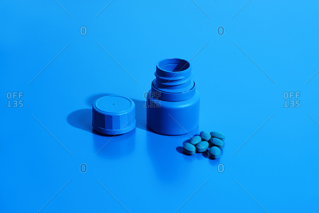An open blue pill bottle and some blue pills on a blue background with some blank space around them