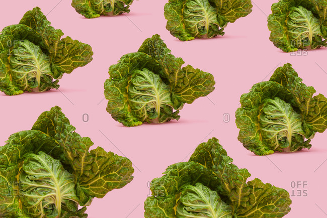 A mosaic of some green cabbages on a pink background