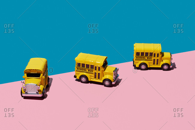 Some toy school buses on a pink and blue background
