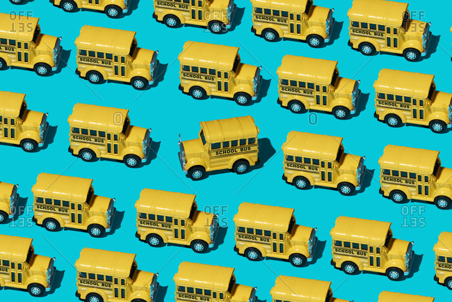 A mosaic of some toy school buses on a blue background