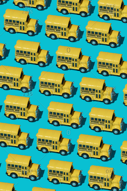 A mosaic of some toy school buses on a blue background, vertical