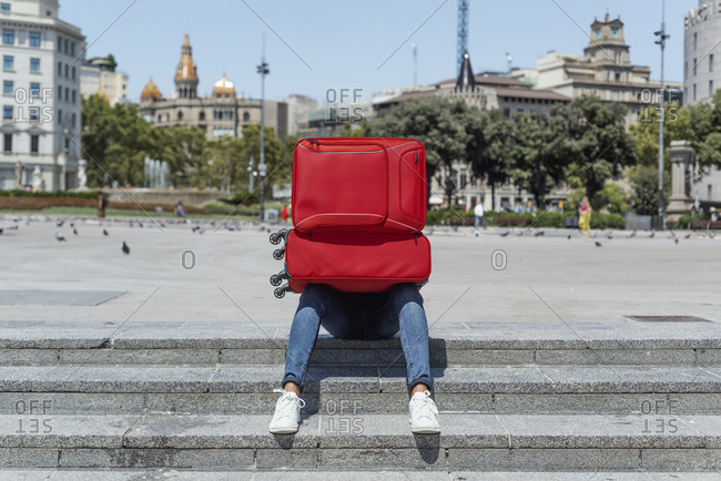Man in jeans opening a red trolley bag in front of him sitting in a staircase in Catalunya Square in Barcelona, Spain