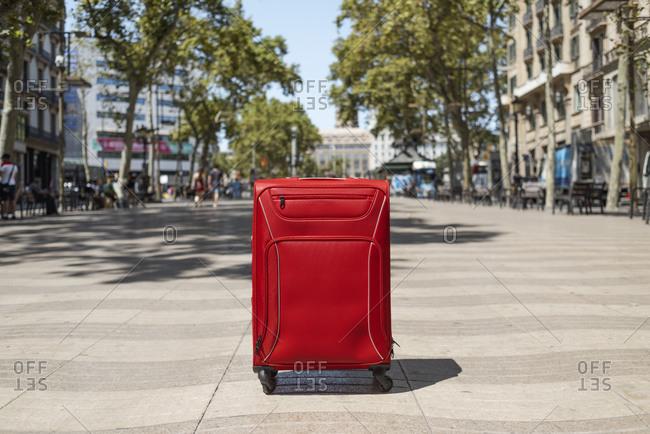 A lonely red trolley bag in the popular Las Ramblas in Barcelona, Spain
