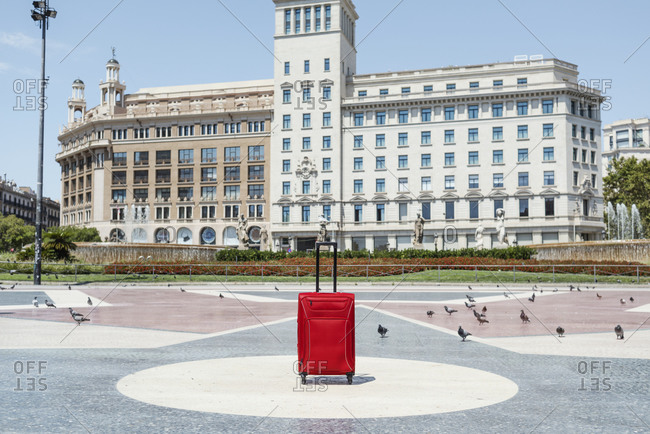 A lonely red trolley bag in a deserted Catalunya Square in Barcelona, Spain