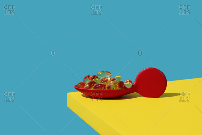 Yellowish transparent pills in a red spoon, on a bright yellow table, against a blue background with some blank space on top