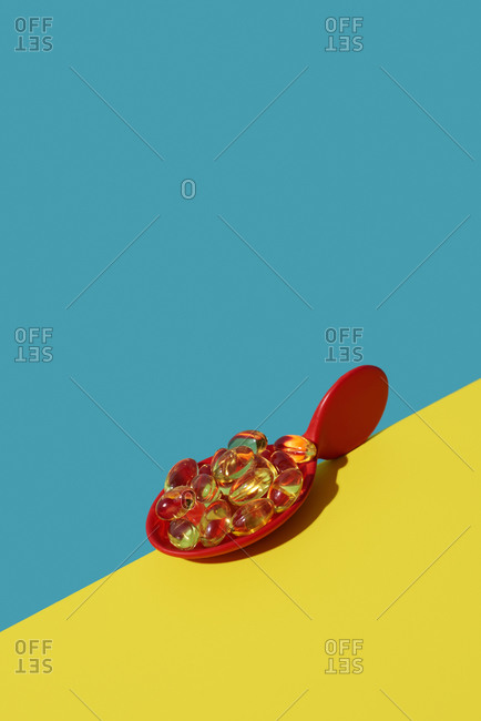 Yellowish transparent pills in a red spoon placed on the edge of a bright yellow table, in diagonal against a blue background with some blank space on top, vertical