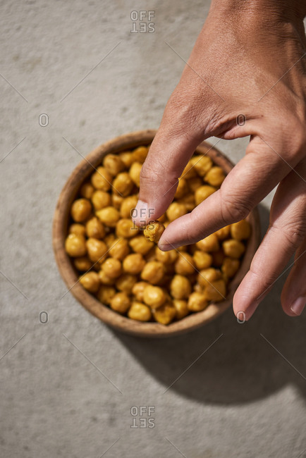High angle view of a man taking a cooked chickpea, seasoned with curry powder, from a wooden bowl placed on a rustic gray surface