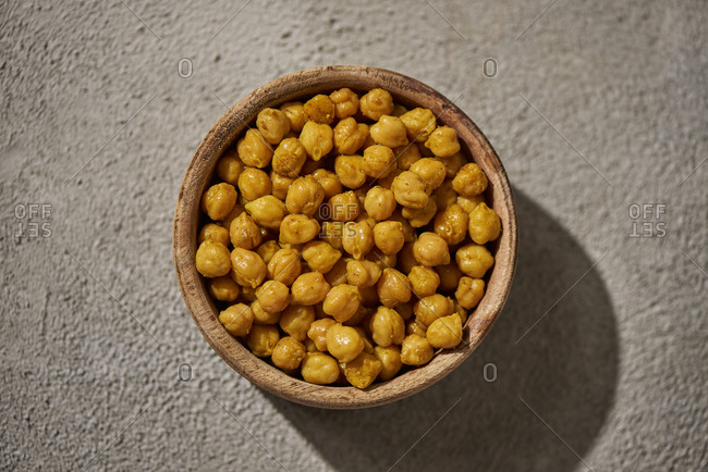 High angle view of a wooden bowl with cooked chickpeas, seasoned with curry powder, on a rustic gray surface