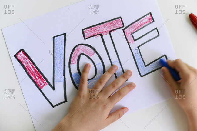 Child's hands coloring Vote sign