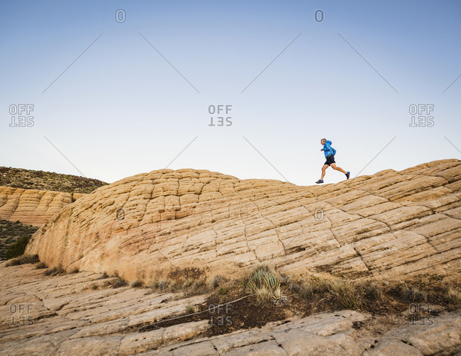 USA, Utah, St. George, Man running in rocky landscape