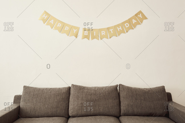 Happy birthday wishes on wall above sofa