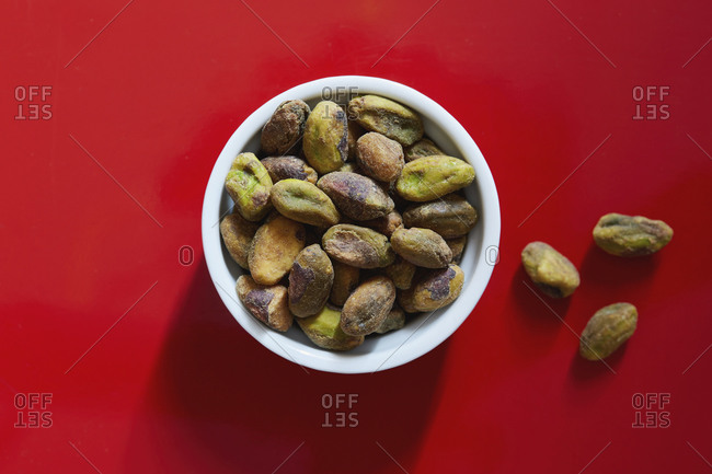 Pistachios in bowl on red background