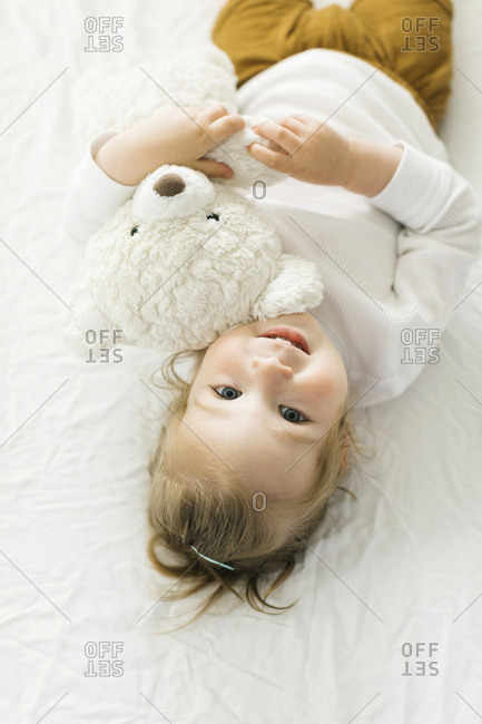 Smiling toddler girl lying on bed with teddy bear toy