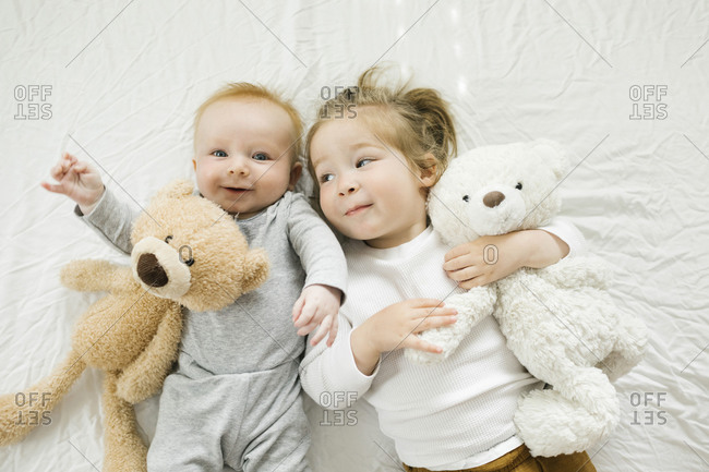 Portrait of siblings lying on bed with their teddy bears