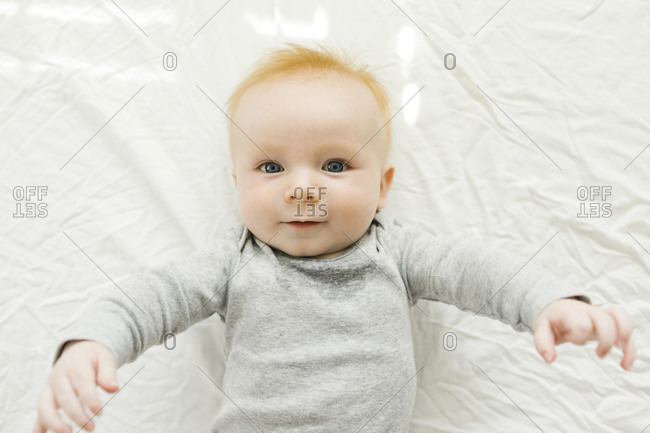 Portrait of baby boy lying on bed