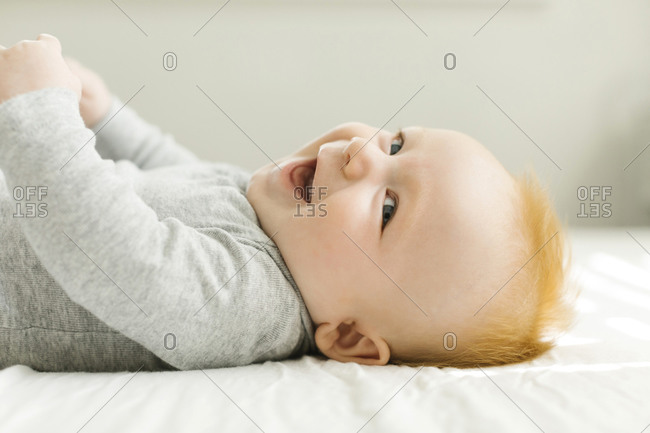 Smiling baby boy lying on bed