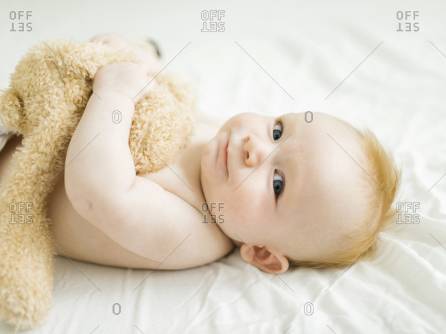 Portrait of baby boy lying on bed with teddy bear