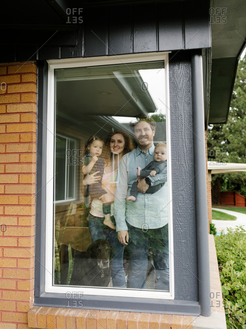 Family with children (6-11 months, 2-3) looking through window