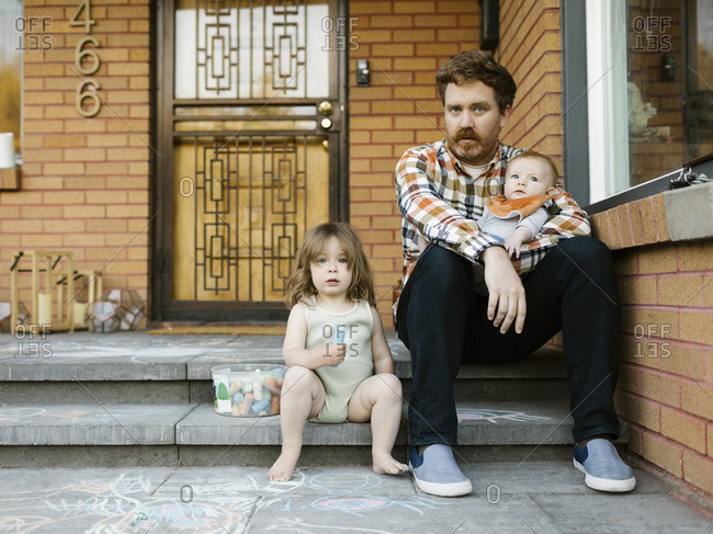 Father sitting on porch with daughter (2-3) and son (6-11 months)