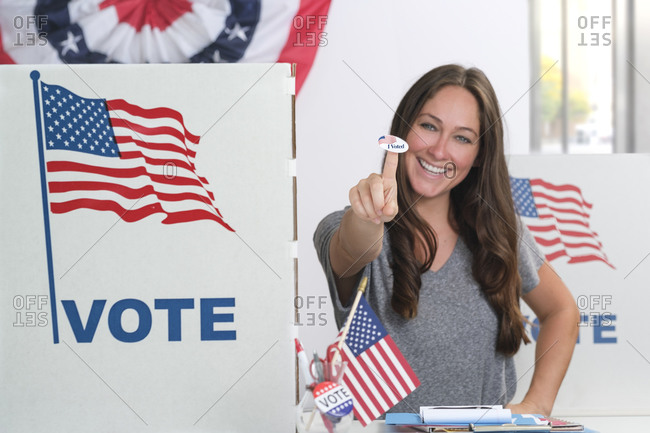 Caucasian woman holding voting sticker