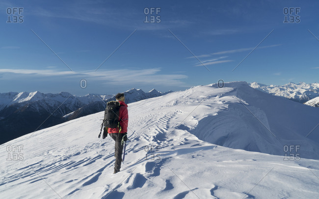 Italy, Piedmont, Alps, Monte Rosa, Climber reaching snow covered mountain top