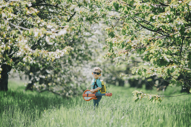 Boy (2-3) holding toy instruments in orchard