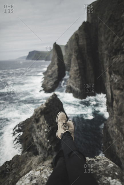 Denmark, Faroe Islands, Sorvagur, Low section of person on sea cliff