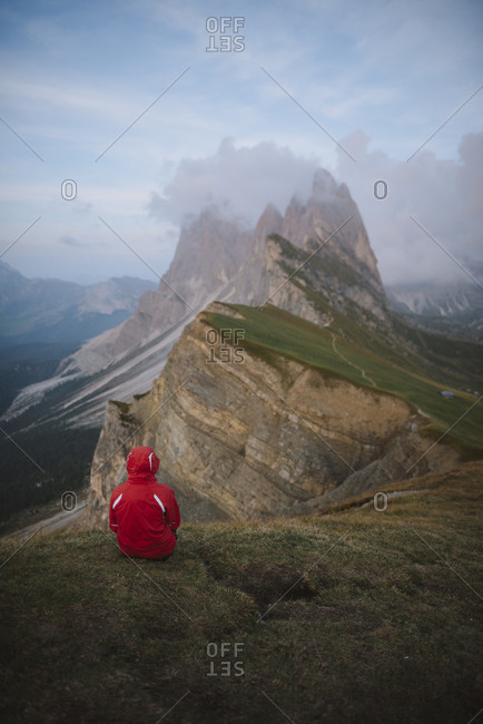 Italy, Dolomite Alps, Seceda mountain, Person sitting on grass looking at scenic view of Seceda mountain in Dolomite Alps