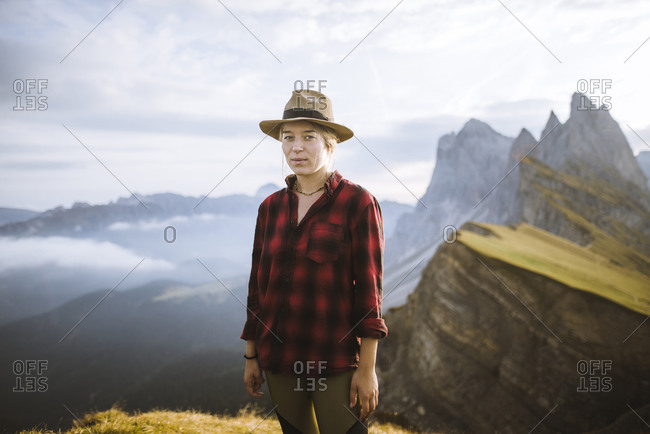 Italy, Dolomite Alps, Seceda mountain, Portrait of woman in hat hiking near Seceda mountain in Dolomites