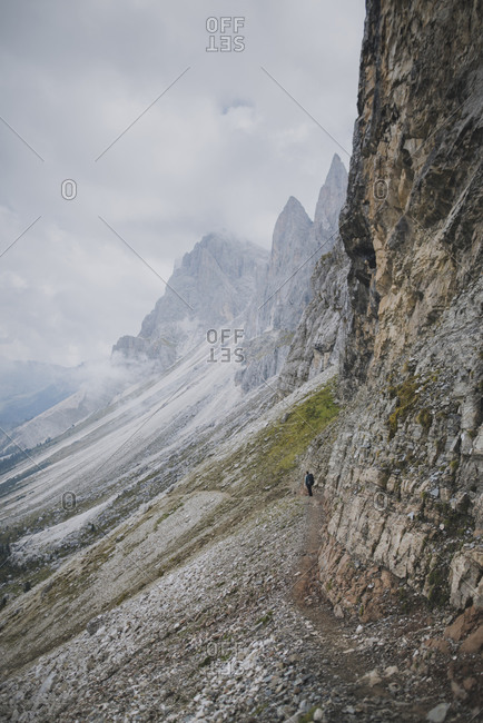 Italy, Dolomite Alps, Seceda mountain, Man with backpack hiking near Seceda mountain in Dolomites