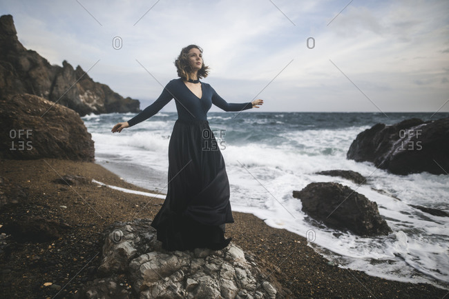 Ukraine, Crimea, Young woman standing on rocky beach
