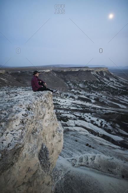 Ukraine, Crimea, Hiker sitting on edge of steep cliff near White Mountain