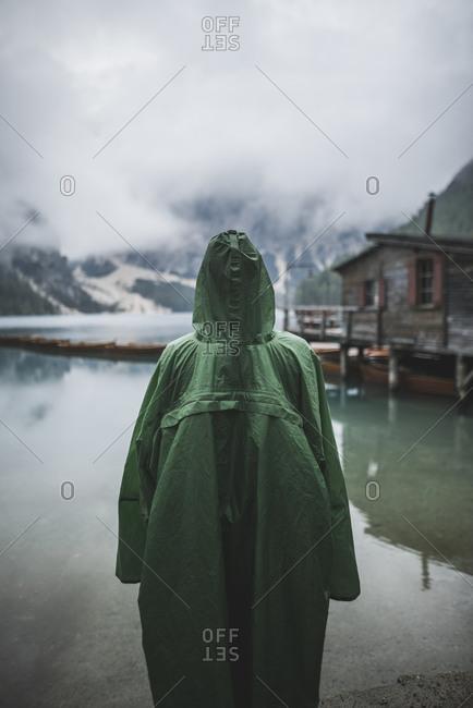 Italy, Man in raincoat standing Pragser Wildsee