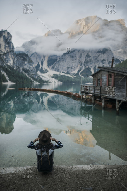 Italy, Woman sitting by Pragser Wildsee in Dolomites