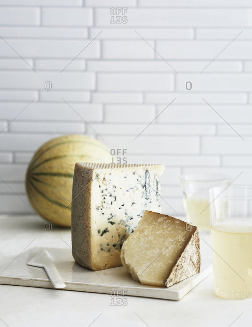 Aged cheese and melon on a white kitchen counter