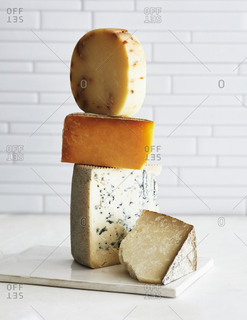 Aged cheese stacked on a white kitchen counter