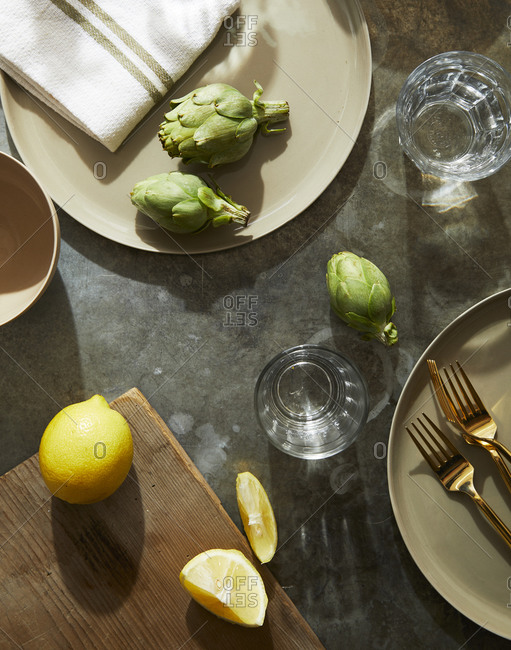 Artichokes and lemons on gray tabletop