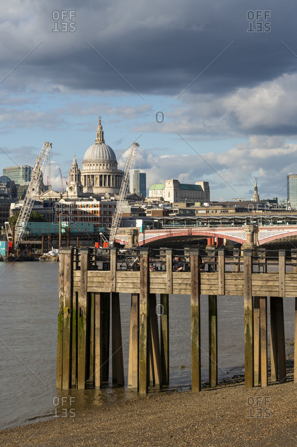 London, United Kingdom - July 6, 2020: View of St. Paul's Cathedral and the City of London above old wooden pier on the Southbank of the River Thames