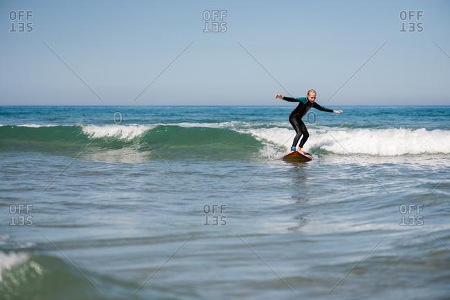 Young preteen girl surfing in the ocean