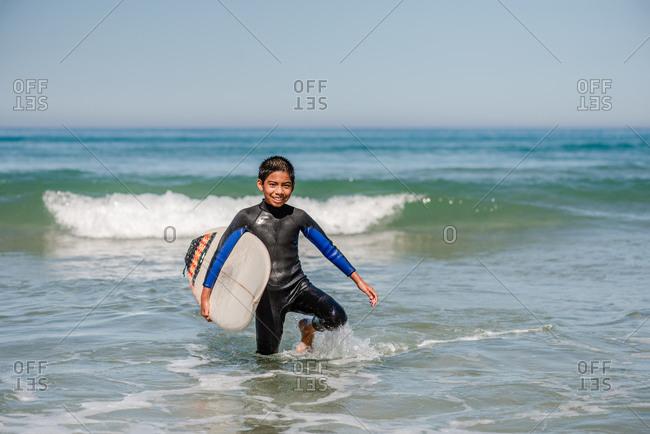 Boy walking with surfboard in the ocean