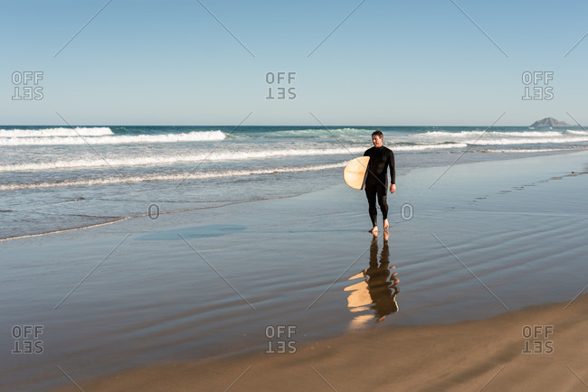 Middle-aged man in a wetsuit with surfboard on the beach