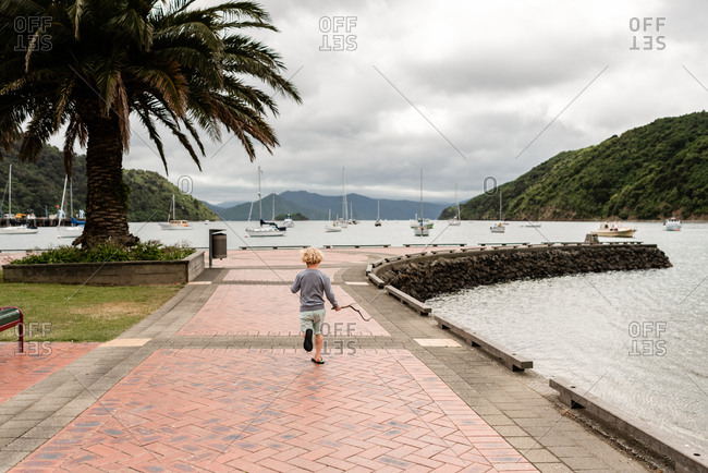 Boy running with stick on promenade by sailboat harbor