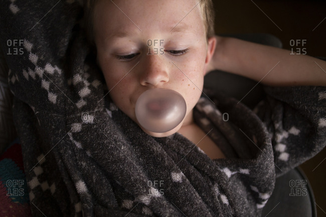 Overhead view of boy lying down blowing a bubble with gum