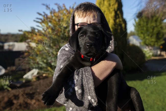 Boy holding a black puppy outdoors