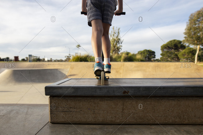 Back view of child riding scooter at the skatepark