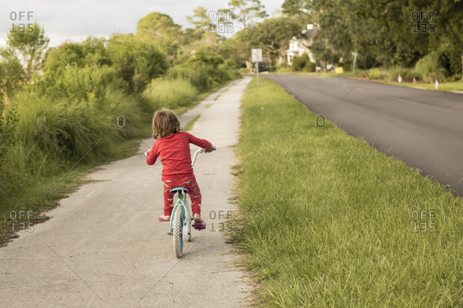 A five year old boy in a red shirt riding his bike on a quiet residential street.