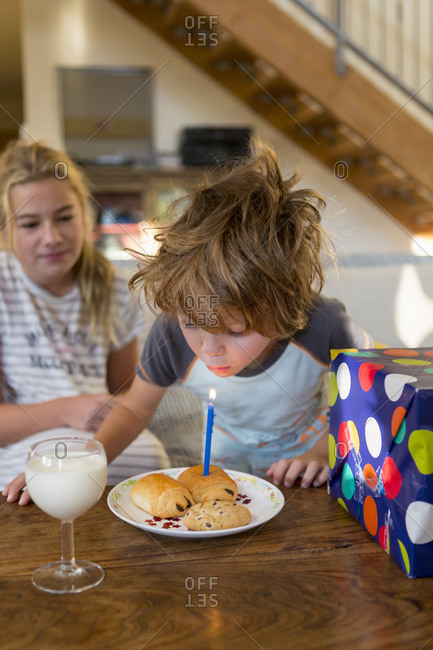 5 year old boy blowing out candle on croissant